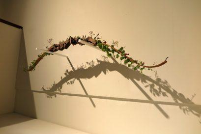 張納祈同學的作品「放下」對戰爭的正當性提出質問,並透過親手雕刻的弓箭與裝置上的植物來表達「愛」才是能讓紛爭得以消弭的最終答案。
