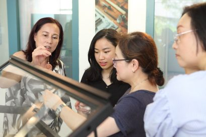 学院讲师陆换芝(左一)与学员一起介绍展品。