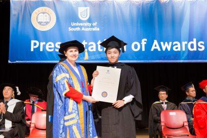 南澳大学校监Ms. Pauline Carr 向毕业同学颁发学士学位证书。