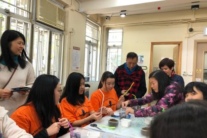 扶康会「香港最佳老友」运动服务经理张仙珍(左一)及多位以「助教」身分的智障人士带领同学一同学习栽种、设计园景。